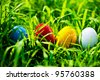 Four colored easter eggs on the meadow - stock photo