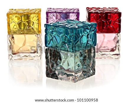 four colored glass bottles of perfume on a white background with the reflection. - stock photo