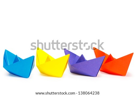 Four colored paper ships on a white background - stock photo