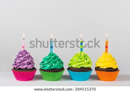 Four colorful cupcakes decorated with birthday candles and sprinkles. - stock photo