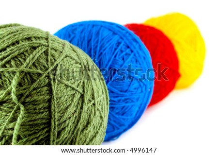 Four colorful knitting balls over white background.