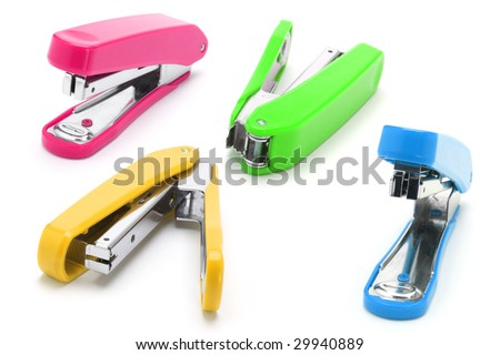 Four colorful staplers arranged on white background