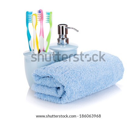 Four colorful toothbrushes, liquid soap and towel. Isolated on white background