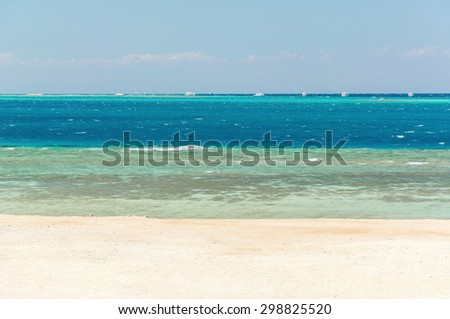 four colors of summer - sand, reef, sea and sky - stock photo