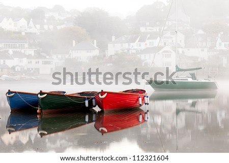 Four colourful boats on a very misty morning.  Taken at dawn in Newton Ferrers, Devon. - stock photo