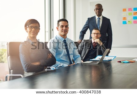Four confident successful multiracial diverse business partners or associates seated at a boardroom table having a meeting and pausing to smile at the camera - stock photo