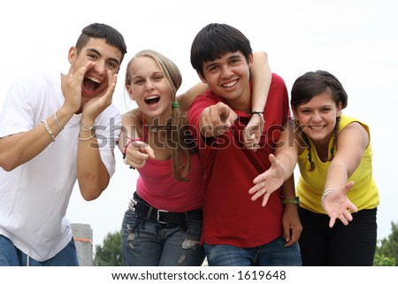 four confident teenagers reaching out - stock photo