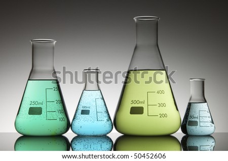 four conical flasks with green and blue liquid with a white background