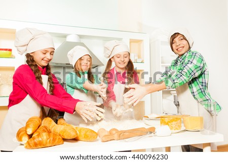 Four cooks kneads flour and eggs for bakery dough - stock photo