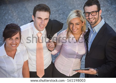 Four corporate people posing smiling on a street