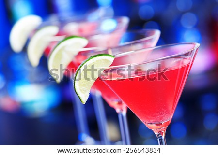 Four cosmopolitan cocktails on a bar counter - stock photo