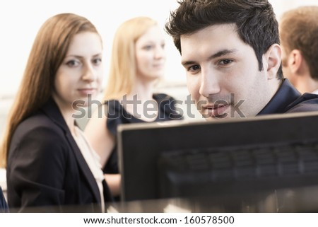 Four coworkers sitting and discussing in the office by computer monitors