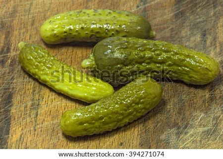 Four crispy pickled cucumbers on a rough wooden background - a cutting board. Close-up selective focus image - stock photo