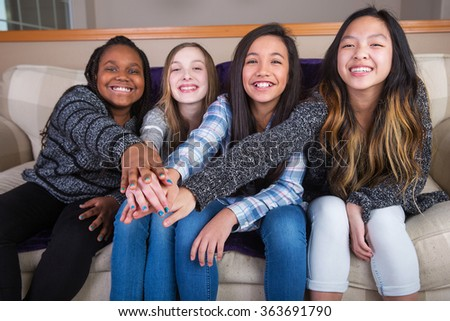 Four culturaly diverse girls holding hands in unity - stock photo