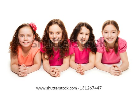 Four cute teen girls in pink laying on the floor, smiling and look happy, isolated on white