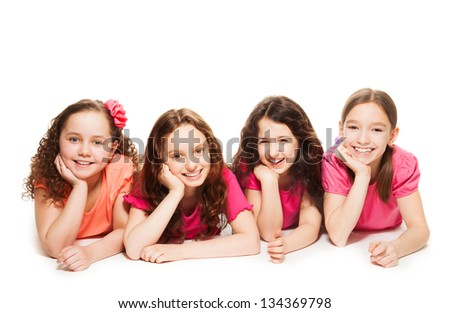 Four cute 10 years old girls in pink laying on the floor, smiling and look happy, isolated on white