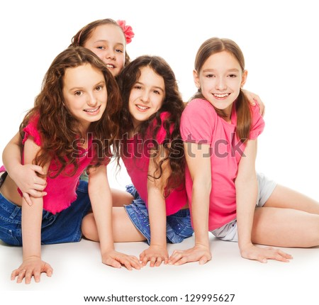 Four cute 10 years old girls in pink sitting and hugging on the floor, smiling and look happy, isolated on white