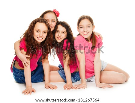 Four cute 10 years old girls in pink sitting, smiling and look happy, isolated on white