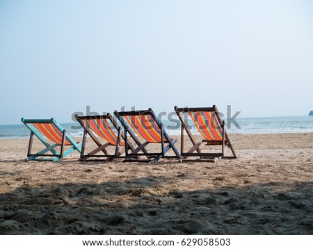 Four deck chairs on beach