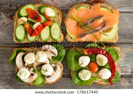 Four delicious open wholewheat sandwiches on a wooden picnic table topped with smoked salmon, avocado, mushrooms, cucumber , baby spinach and mozzarella cheese - stock photo