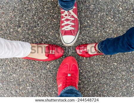 Four different pair of red shoes on the sand asphalt - stock photo
