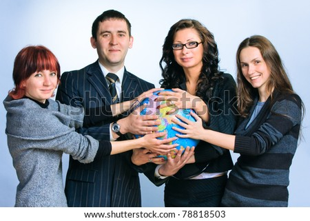 Four different people hold the globe in their hands - stock photo