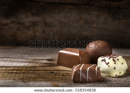 Four different types of chocolate candy over rustic wooden background