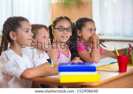 Four diligent pupils sitting in row and studying at classroom - stock photo
