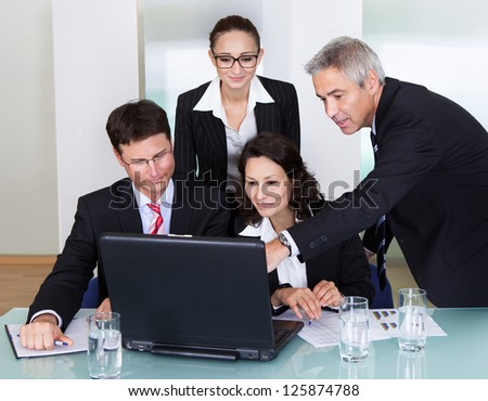Four diverse professional businesspeople having a discussion and brainstorming session gathered around a laptop computer - stock photo