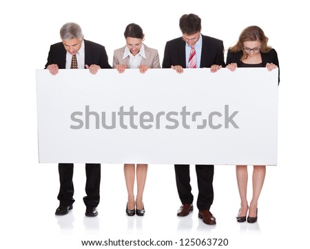Four diverse professional businesspeople holding a blank banner or horizontal sign for your text or advertisement isolated on white - stock photo