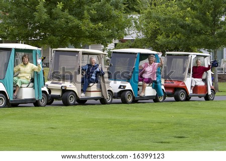 Four elderly women waving while driving golf carts. Horizontally framed photo.