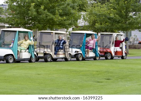 Four elderly women waving while driving in golf carts. Horizontally framed photo.