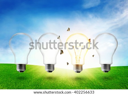 Four electric light bulb on grassland. Eco energy concept.