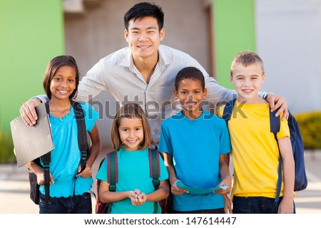 four elementary school students and teacher on campus