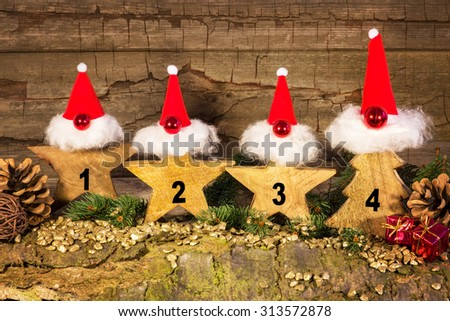 Four elves with red hats sitting in front of a wooden background - stock photo