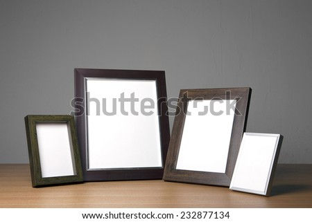 four empty(blank) wood photo frames(walnut, steel) on the wood table(desk) at the studio. - stock photo