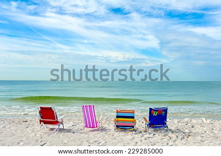 Four Empty Bright Color Beach Chairs on the Beach - stock photo