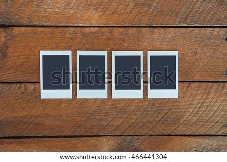 Four empty instant photo frames with copy space, high angle view on wood table