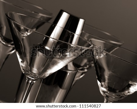 Four empty martini glasses and a shaker