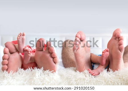 Four family feet - father, mother, baby boy and baby girl - stock photo