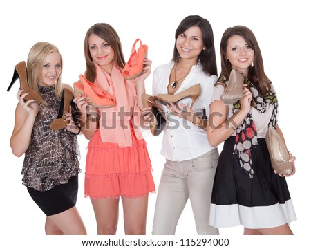 Four fashionable girls holding their shoes isolated on white - stock photo