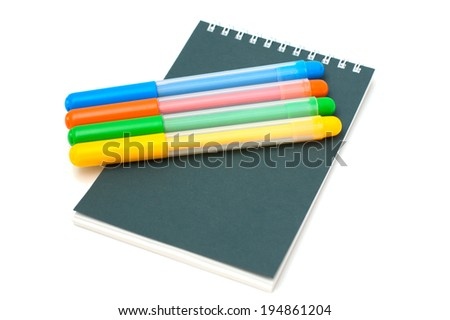 four felt-tip pens on notebook isolated - stock photo