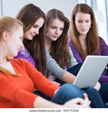 Four female college students using a laptop computer,  working on their homework on campus (color toned image)