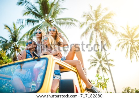 four female friends sitting on top of off-road truck in jungle enjoying koh samui thailand together shot with lens flare