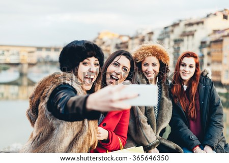 Four female friends taking a selfie on a bridge in Florence, Tuscany. Behind them the beautiful Ponte Vecchio. The women are dressed in winter jackets and hats against the cold of winter - stock photo