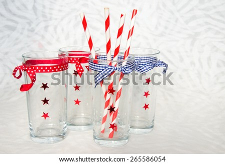 Four festive glasses with decorative stars and striped straws in one of them