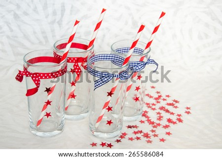 Four festive glasses with decorative stars and striped straws, view from above