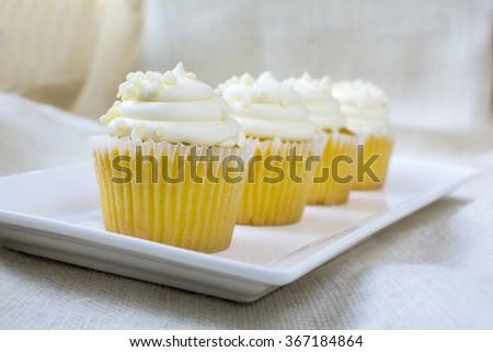 Four french vanilla cupcakes and creamy vanilla icing with white chocolate bite topping. Vanilla cupcake dessert - stock photo
