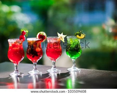 Four fresh drinks with strawberry and mint at the table outdoor - stock photo