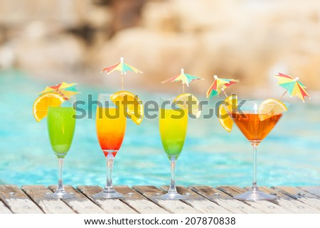 Four fresh fruit cocktails on wooden planks in front of a blue swimming pool  - stock photo